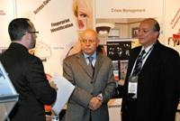 A GNSS executive speaks with customers at their stand at Intersec 2009