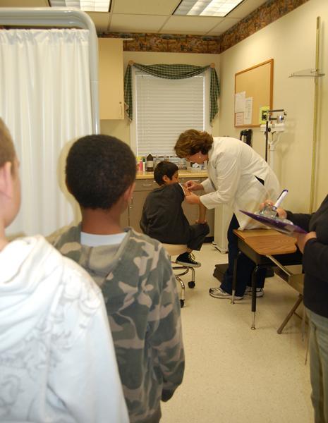 Hillsides Nurse Kim Weleba gives children living at foster care children's charity flu shots.