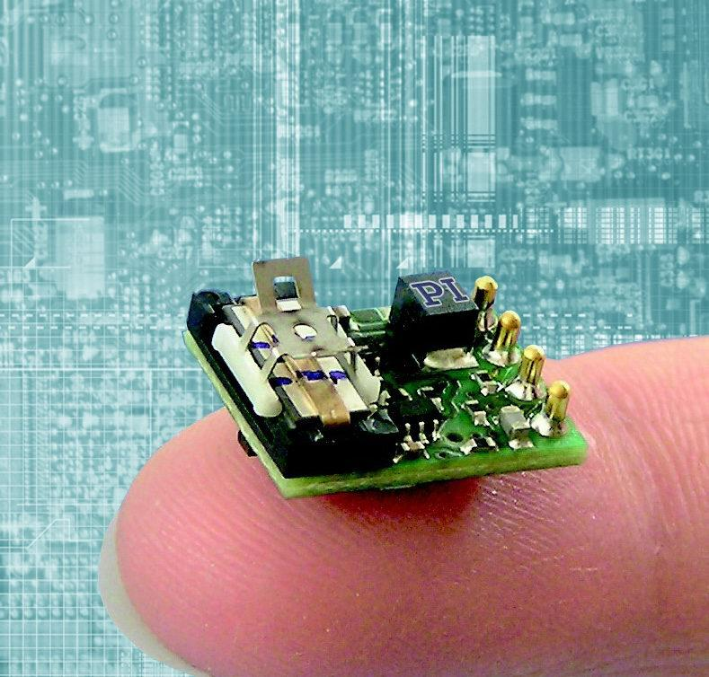 P-653 Linear Motor Slide w/ driver board shown on a human finger for size comparison.