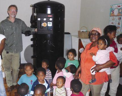 Orphans and their carers stare at the large fresh water tank as a component of the solar system