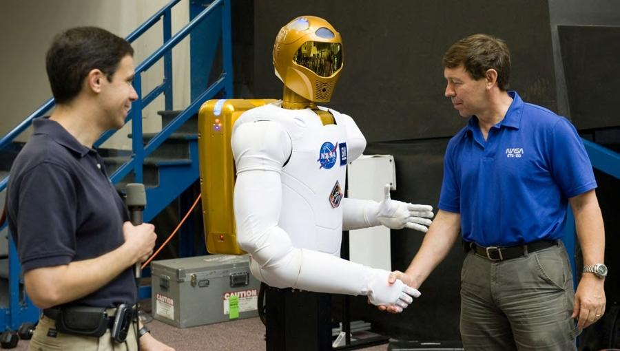 The Robonaut 2 sees what it is doing thanks to HALCON. NASA astronaut Michael Barrett shakes hand with R2 harmlessly.