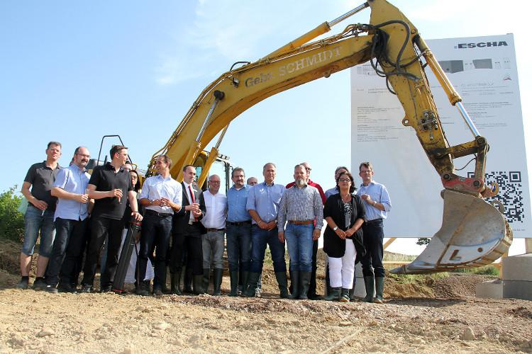 Guests and staff celebrate the ground-breaking. Instead of a spade, the big excavator shovel starts its work immediately