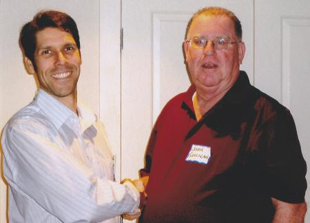 Chris Lehmann (L) accepts the BNI Rainmakers leadership role as President for 2012-2013 with a handshake from John Sullivan (R)