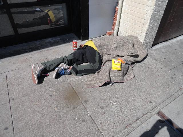 Homeless person layign on sidewalk in Berkeley California with food from outreach group