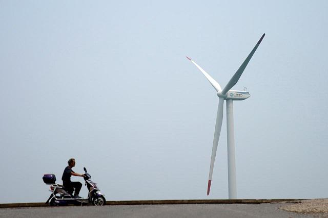 A man rides an electric scooter past a wind turbine in Shanghai, China August 11, 2017. REUTERS/Aly Song