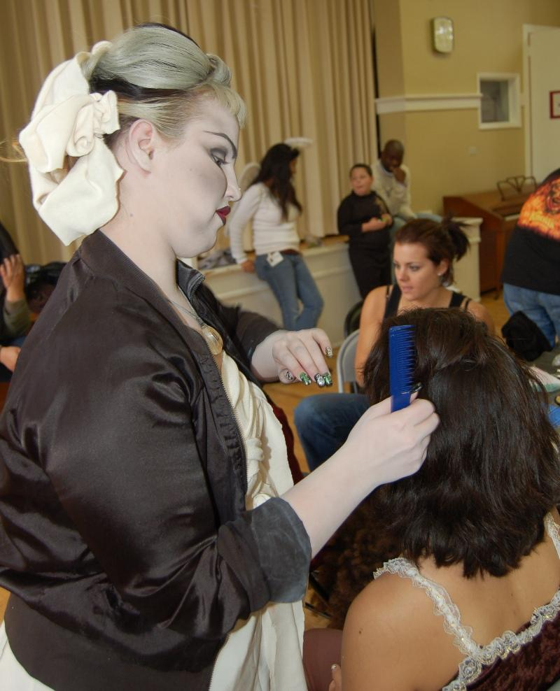 A student at the Westmore Academy of Cosmetic Arts does the hair of a Hillsides child for her Halloween costume